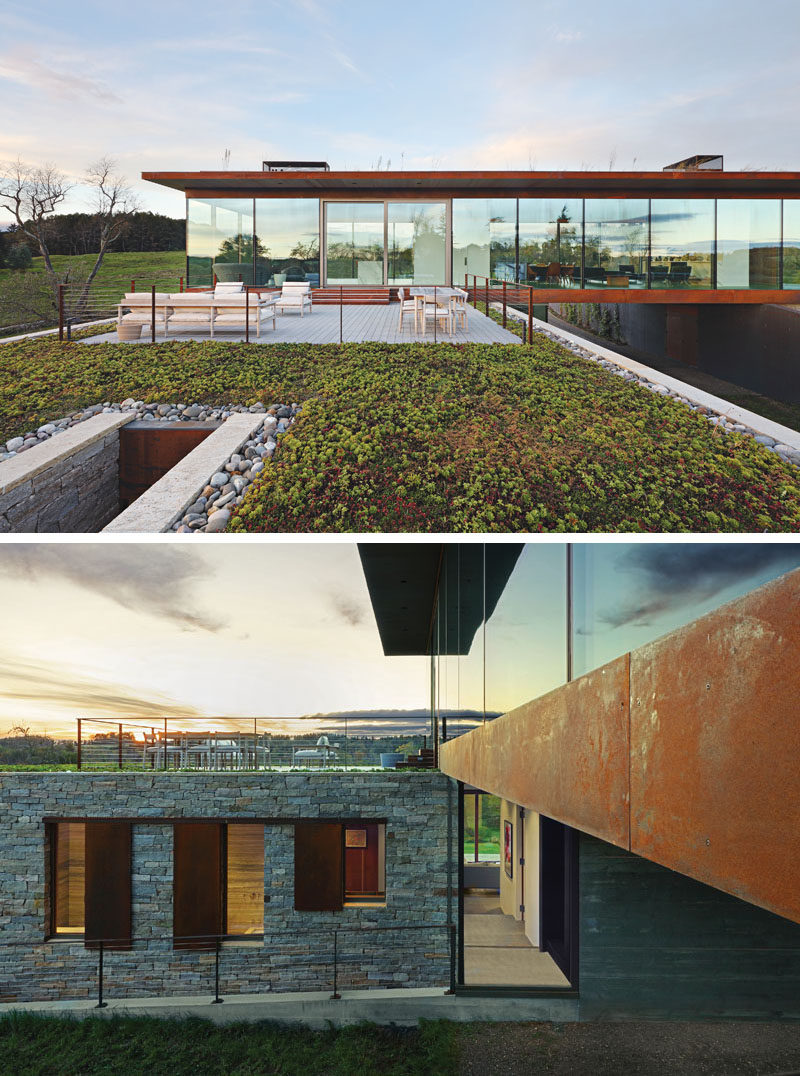 A large sliding door off the kitchen of this modern house leads out to a deck and green roof. Below the green roof is the lower volume of the house thatuses stone and eventually plantings/vines to blend with the ground. #ModernHouse #Deck #GreenRoof