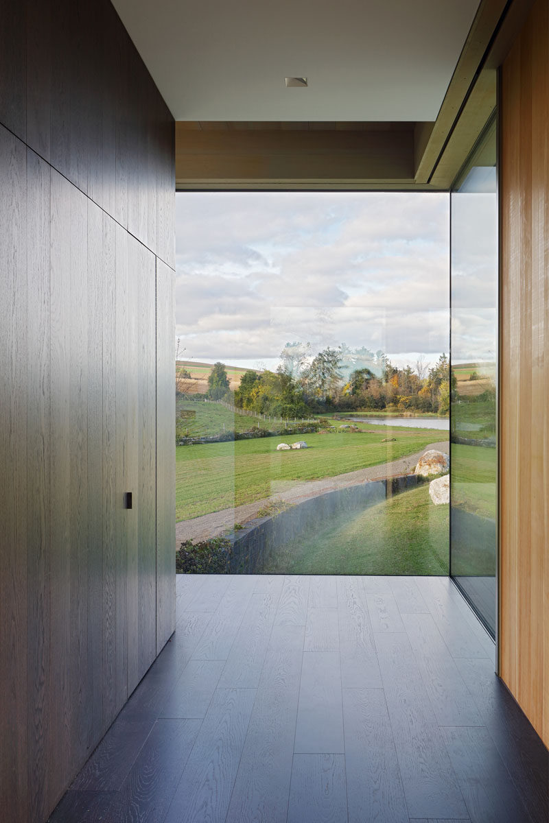 Inside this modern house, a dark wood wall with a hidden closet guides visitors to walk towards the windows, perfectly framing the view. #Windows #Entryway