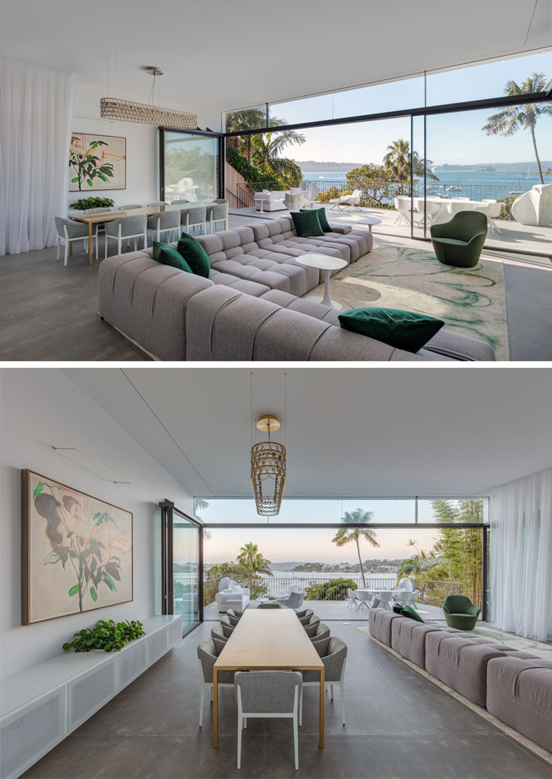 The social areas of this modern house take full advantage of the water view, with the dining room and living room opening up to a deck with additional living space. #ModernInterior #LivingRoom #Deck