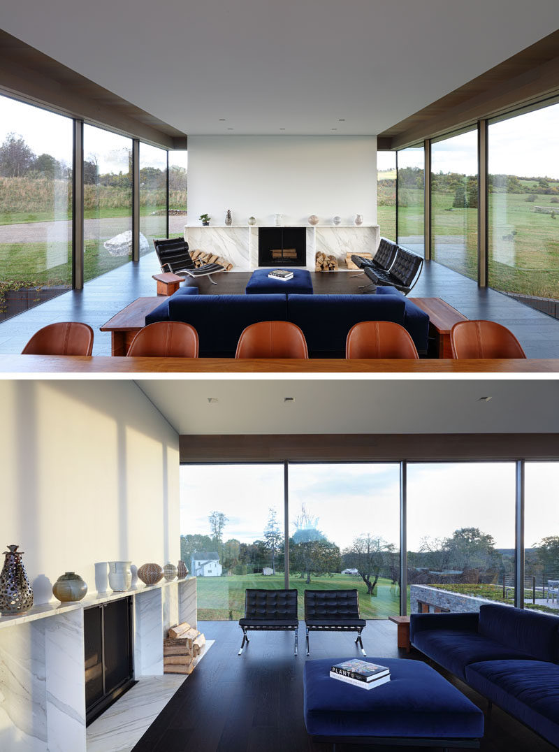 The main floor of this modern house opens up to the dining room and living room. A white wall with a fireplace and wood storage separates the living room from the entryway. #ModernLivingRoom #Fireplace