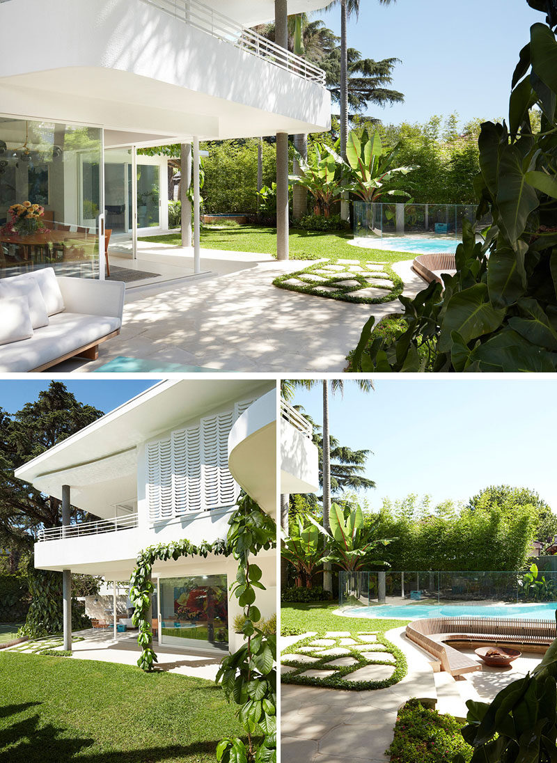 The sliding glass doors of this modern house open up to the backyard, where there multiple seating areas and a swimming pool. #Backyard #OutdoorSeating #OutdoorLounge #SwimmingPool