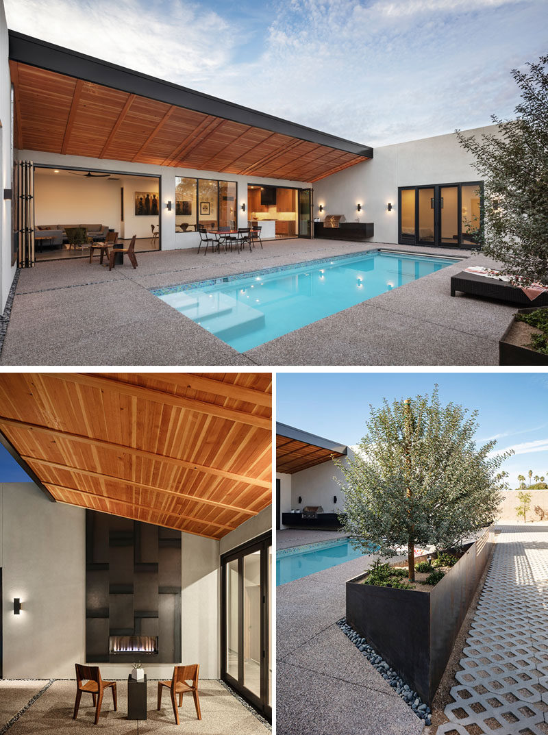 The rear private courtyard of this modern house revolves around a pool, while  a steel-clad outdoor fireplace is located on one side, and on the opposite side, there's a wall hung outdoor kitchen. #SwimmingPool #Courtyard #OutdoorFireplace #Planters