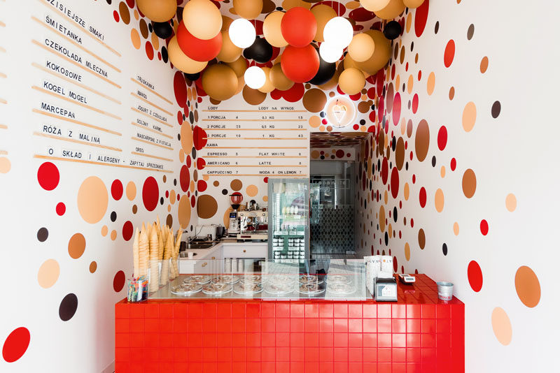 This modern ice-cream shop features colorful suspended balls and lighting from the ceilings, and dots on the walls complement the ball installation on the ceiling. #IceCreamShop #RetailDesign #InteriorDesign