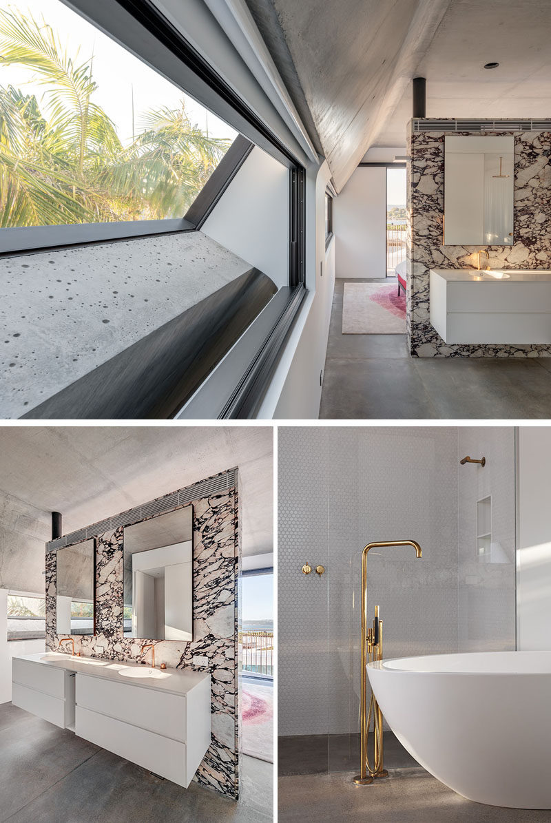 Inside this modern master suite, there's a stone partition wall that separates the sleeping area from the master bathroom. #MasterSuite #BathroomDesign #ModernBathroom