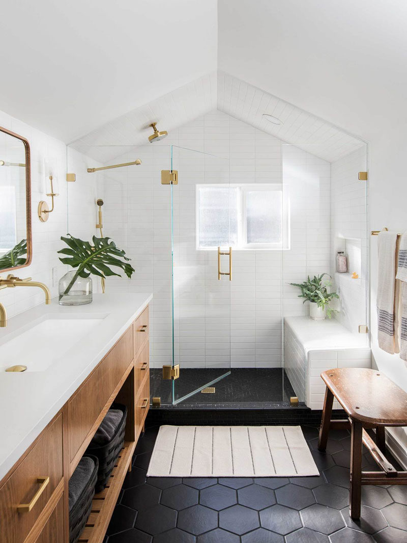 In this modern master bathroom, black hexagonal tiles cover the floor, while a glass shower screen separates the shower from the rest of the bathroom, and brass details add a luxurious touch. #MasterBathroom #ModernBathroom #BathroomDesign