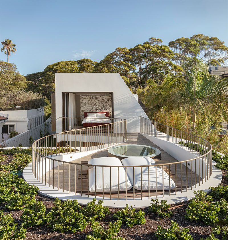 This modern house has a master suite with doors that open to a private rooftop deck surrounded by a green roof. #MasterSuite #RooftopDeck #GreenRoof