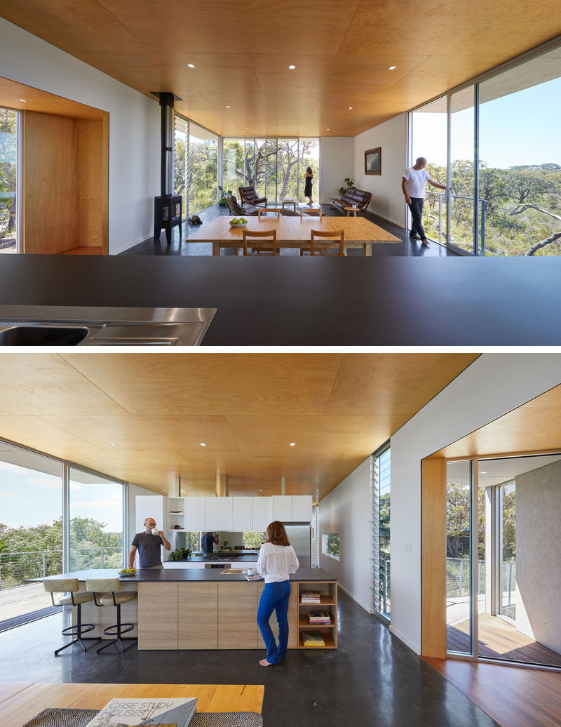 The open floor plan of this living space, dining area, and kitchen, allows the natural light from the floor-to-ceiling windows to filter throughout the home. #OpenFloorPlan #WoodCeiling #ModernKitchen