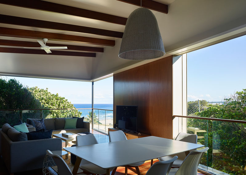 The open plan social areas of this beachside house have sweeping views of the ocean and trees. #OpenPlanInterior #LivingRoom
