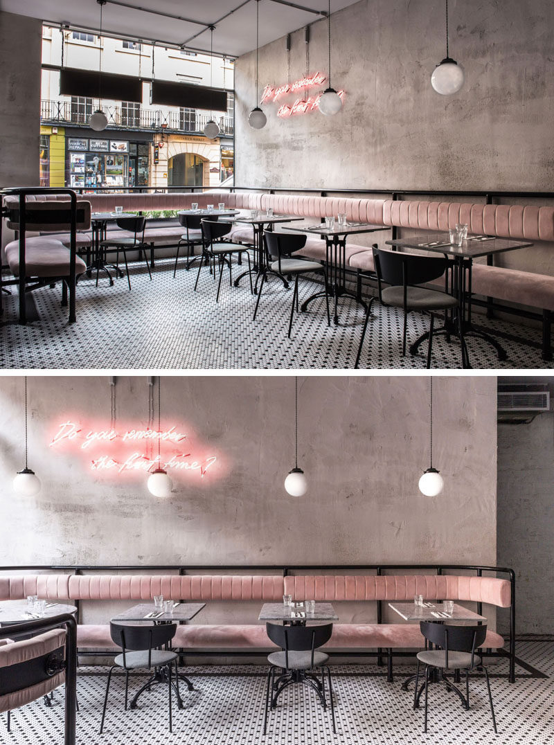 Pale-pink banquettes wrap around the front of this modern restaurant providing lounge seating for bar and restaurant guests, while signature pink neon signage, honed marble tabletops, and black-and-white mosaic flooring, all help to create a fun and welcoming environment. #RestaurantDesign #BanquetteSeating