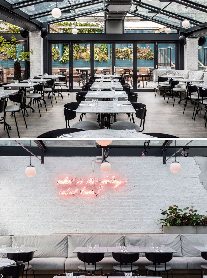 The main dining room of this modern restaurant opens to an alfresco dining area, featuring a glass-atrium roof, whilst an abundance of greenery creates a conservatory-like space. #RestaurantDesign #ModernRestaurant