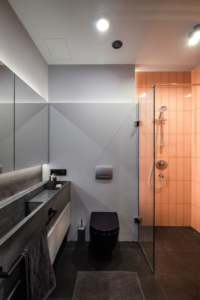 In this modern bathroom, the monochrome palette has been brightened up with the use of a peach subway tile in the shower. #ModernBathroom #BathroomDesign