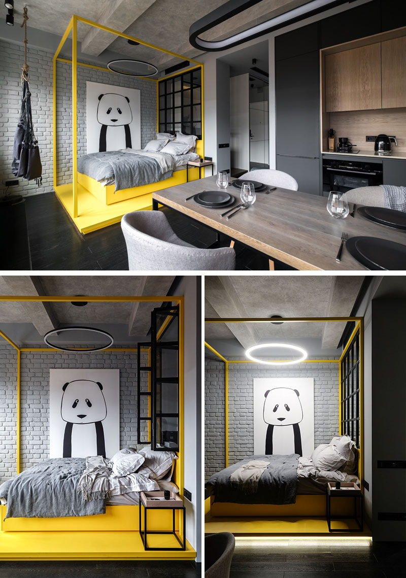 In this modern apartment, a bright yellow pop of color has been added to the monochrome interior in the form of a bed platform and bed frame. The bed sits beside a painted grey brick wall that has a large panda art piece, adding a bit of personality to the space.