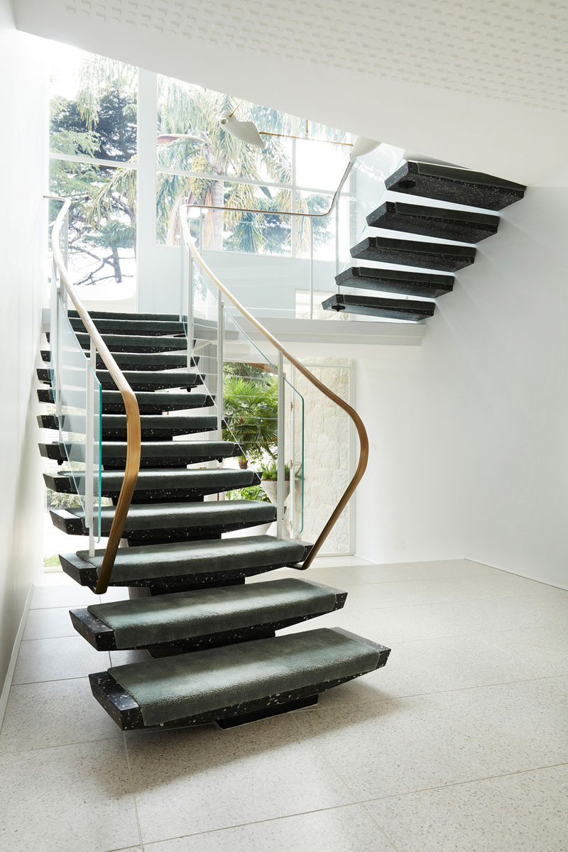 This modern house has white walls with dark stone stairs. #Stairs #StairDesign
