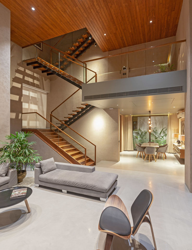 A large wood and steel staircase connects the various levels of this modern house, and leads the eye upwards to the wood ceiling. #ModernStairs #StairDesign