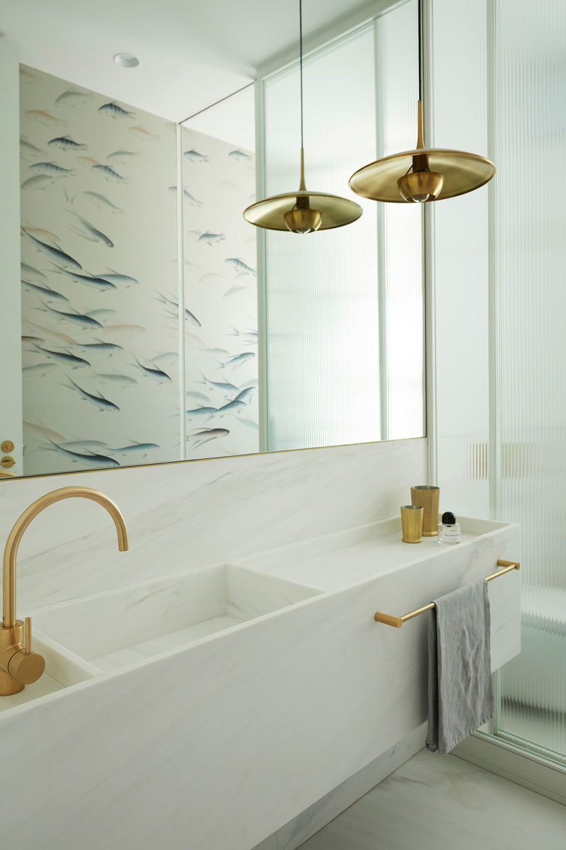In this modern bathroom, a white vanity with a built-in basin sits below a large mirror that reflects the fish pattern on the opposite wall. #ModernBathroom #WhiteBathroom