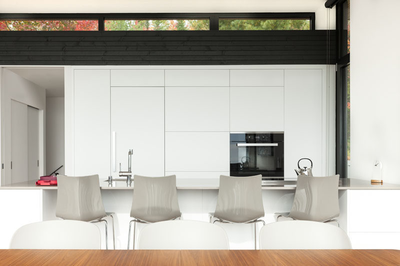 In this modern kitchen, white minimalist cabinets blend in seamlessly with the white walls, and contrast the dark wood accents. #ModernWhiteKitchen #WhiteKitchen #KitchenDesign