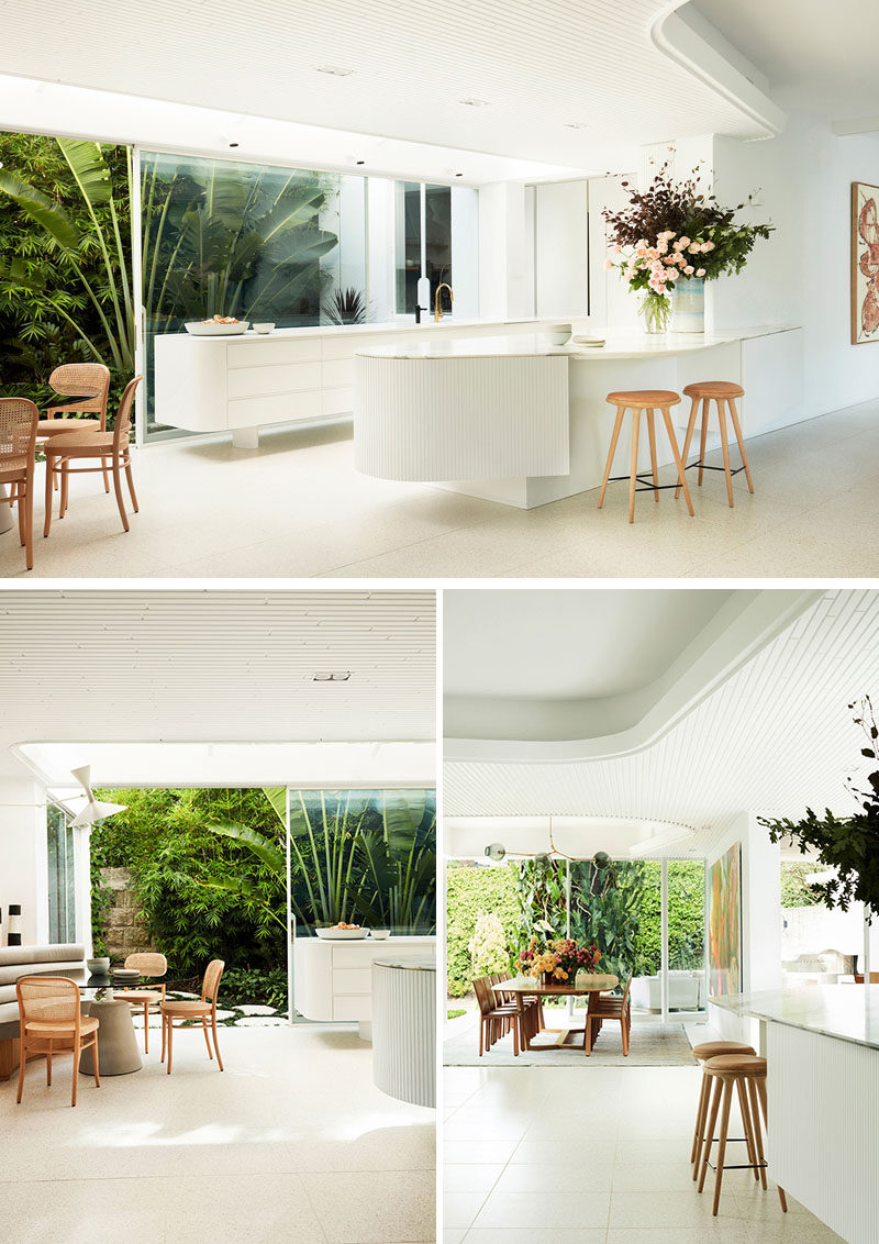 This modern white kitchen sits beside a small breakfast area and a larger dining area. #WhiteKitchen #InteriorDesign #ModernKitchen