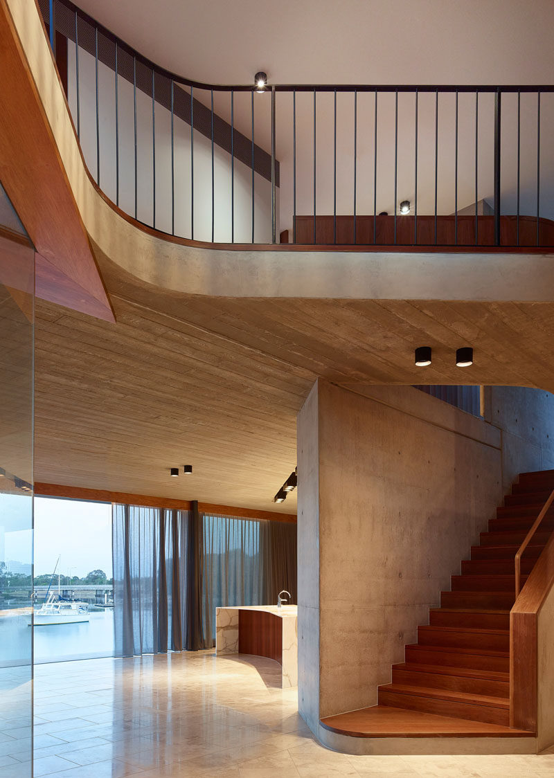 This modern house has board-formed concrete details that add texture to the interior. #WoodStairs #Concrete