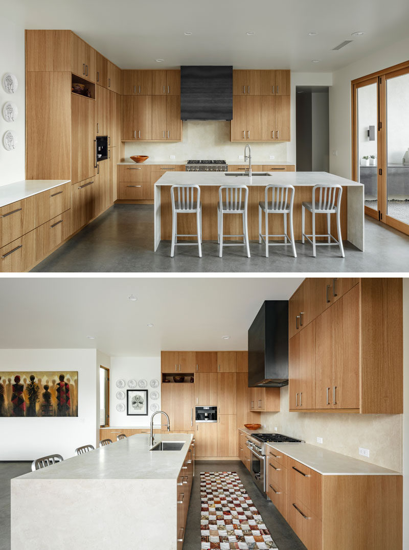 In this modern kitchen, white oak cabinetry has been paired with honed marble counters, and a custom steel hood. Bi-folding doors opens the kitchen to an outdoor space. #ModernKitchen #WoodKitchen #KitchenDesign