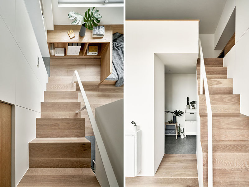 Simple wood stairs with a white handrail lead up to the loft bedroom in this tiny apartment. #Stairs #SmallApartment #TinyLiving