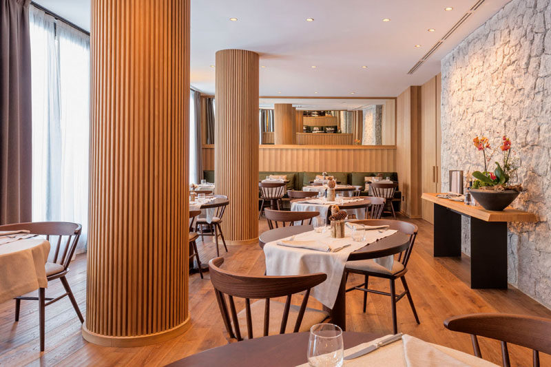The columns in this modern restaurant's dining room have been wrapped in wood slats, hiding the column within, and turning a potential eyesore into a custom design accent. #RestaurantDesign #Columns #InteriorDesign