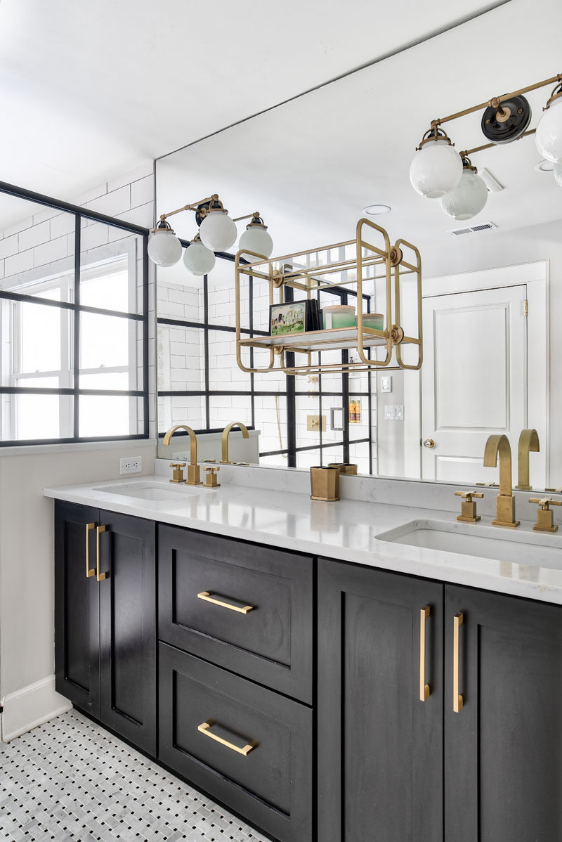 This modern bathroom features a dark vanity with dual undermount sinks, basketweave tile flooring, and a large mirror with a mounted shelf and sconces. #ModernBathroom #BathroomVanity #BathroomDesign