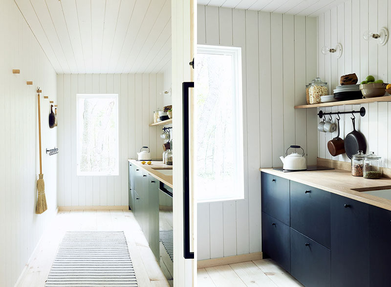 This simplistic and modern kitchen features bleached Eastern Pine floors and walls clad in white painted lap paneling. #KitchenDesign #ModernKitchen #SimpleKitchen