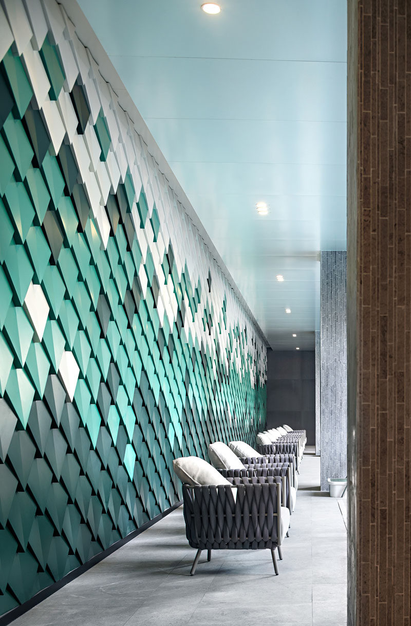 Drawing inspiration from mountains, the designers of this modern outdoor swimming pool area created a wall with custom made aluminum panels installed in a geometric formation, to create an abstract interpretation of mountain ranges. #AccentWall #SwimmingPool #AluminumPanels #MetalShingles