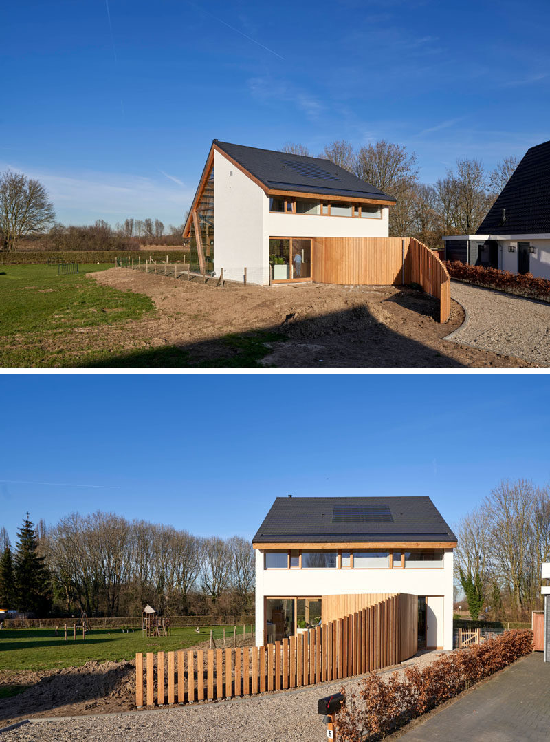 A curved fence guides visitors to the front door of this modern barn-style house. #CurvedFence