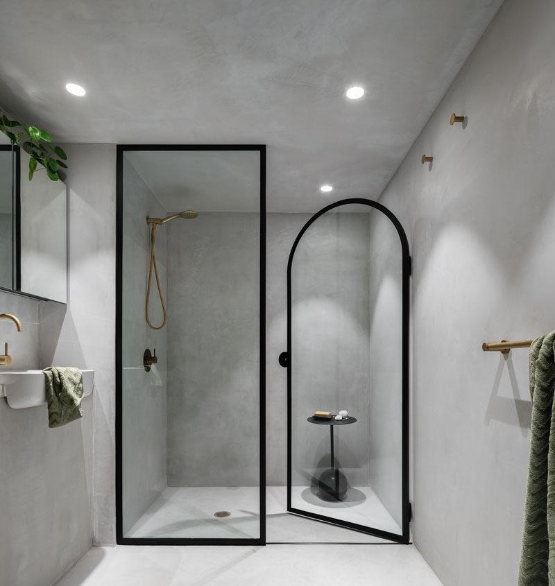 This minimalist bathroom has a black-framed glass shower screen and separate shower door. #ModernBathroom #BathroomDesign