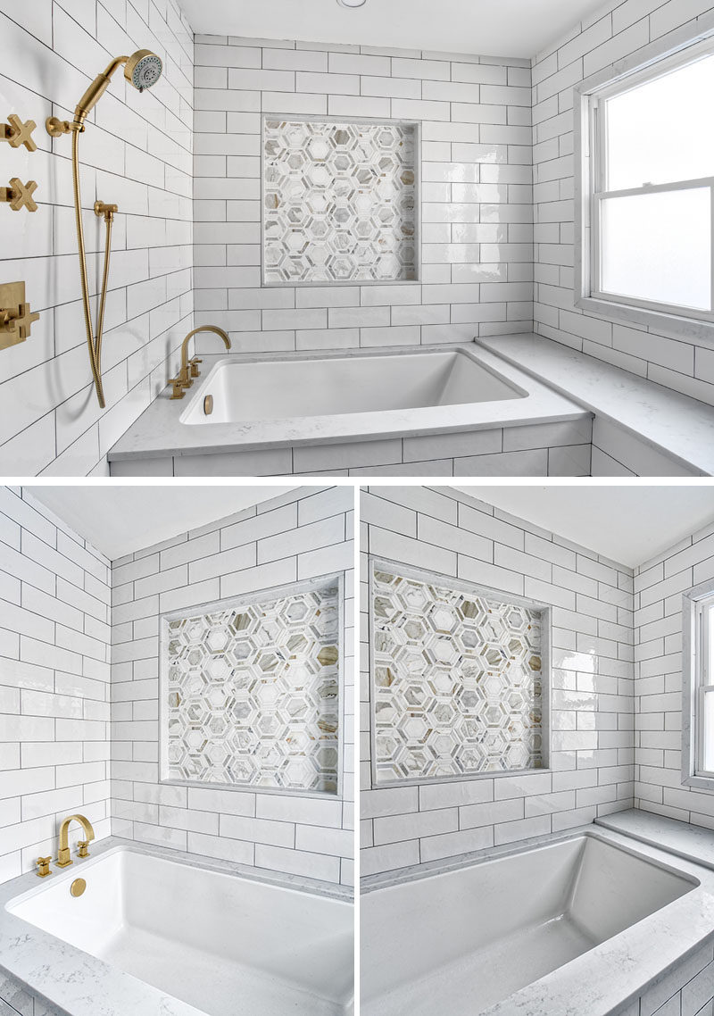 In this modern bathroom, a large undermount style soaking tub issurrounded by a Calacatta marble deck and bench. The accent tile niche breaks up the strong lines of the oversize subway tile surround, and has subtle glints of gold that pick up on the finish of the brass faucets and the hints of gold in the marble. #ModernBathroom #WhiteBathroom #UndermountBathtub #BathroomDesign