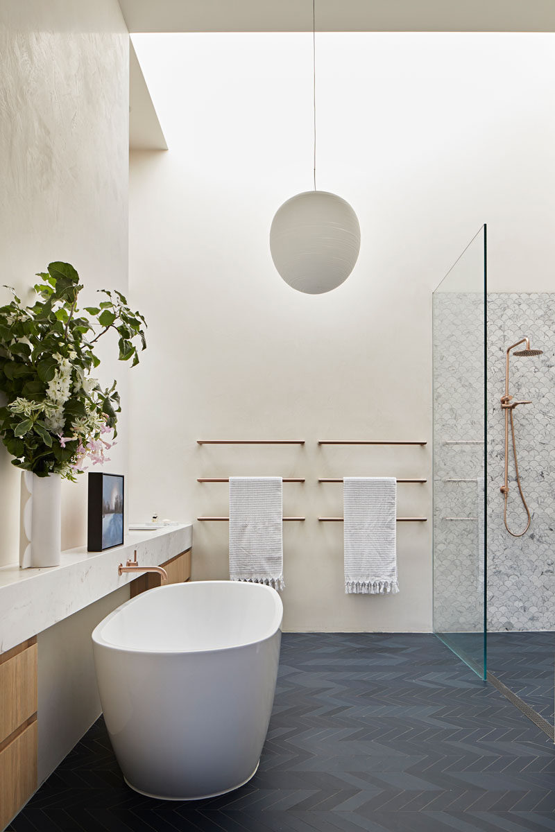 In this modern bathroom, dark grey chevron patterned floors contrast the white walls, while a freestanding bathtub sits opposite the shower. #ModernBathroom #BathroomDesign