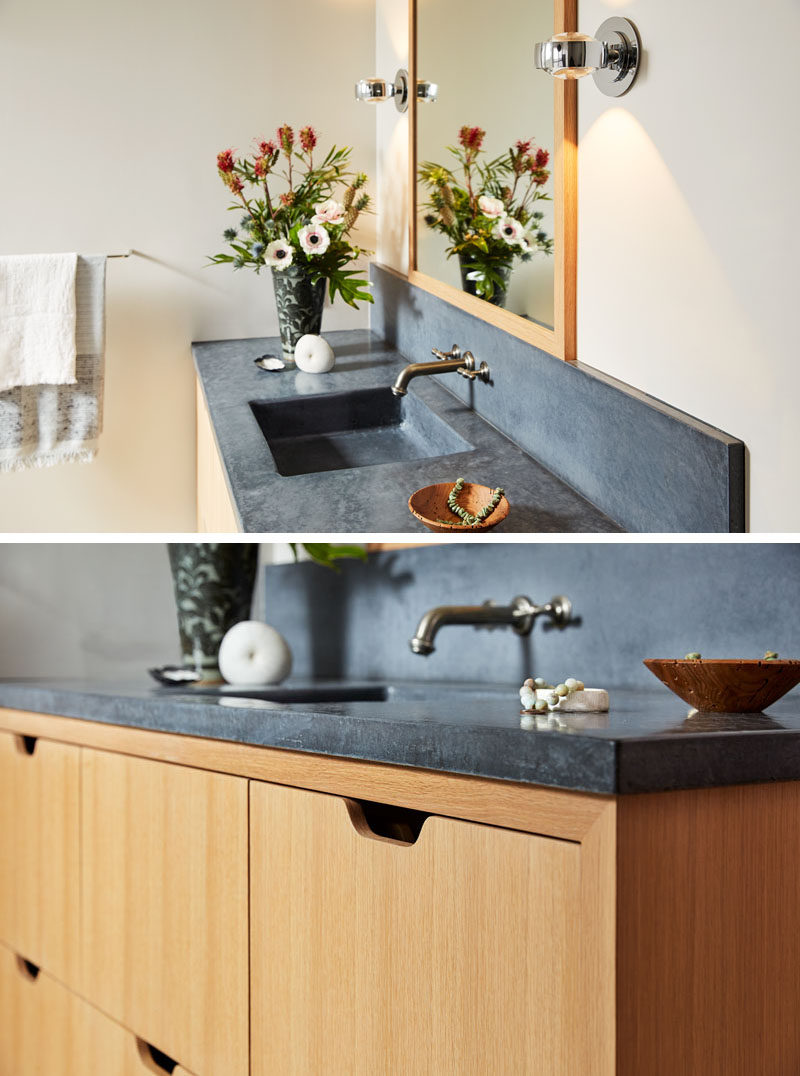 This modern master bathroom features a warm wood vanity with dark concrete counters. #BathroomVanity #Concrete #ModernBathroom