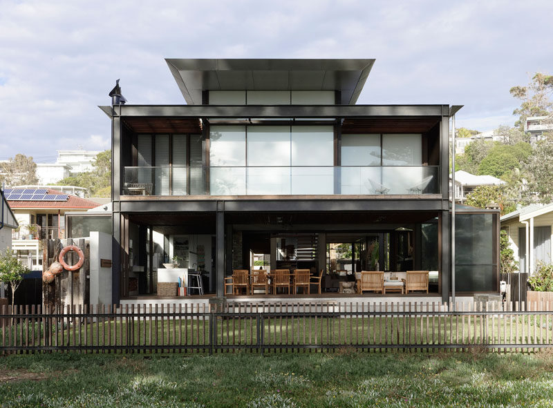 At the rear of this modern house, the verandah, which is enclosable in winter and completely open in summer, provides easy access to the backyard and the beach. #ModernHouse #Verandah #Architecture