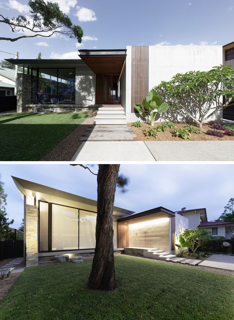 At the front of this modern beach house is a grass courtyard, and a pathway that leads to the front door. #ModernHouse #ModernArchitecture