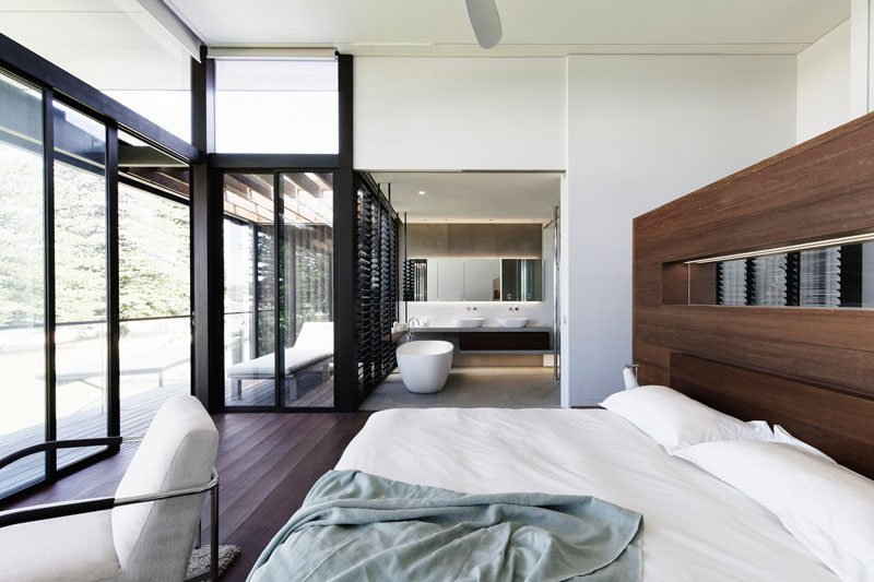 In this modern master bedroom, a rich wood accent wall complements the wood flooring, while the open ensuite bathroom has the bath positioned for views of the water. #MasterBedroom #OpenEnsuite #Bathroom