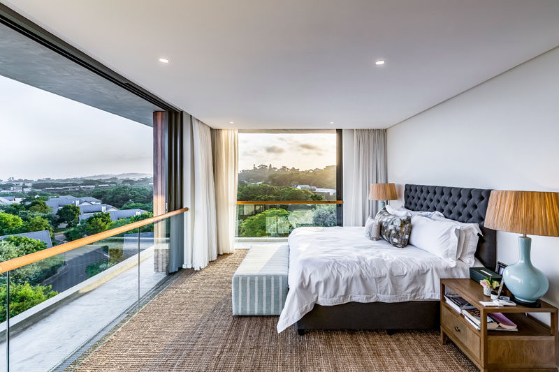 This modern master bedroom takes advantage of being high above the trees, with far-reaching views and sliding glass doors that open to allow a natural air flow, keeping the bedroom cool. #MasterBedroom #SlidingDoors