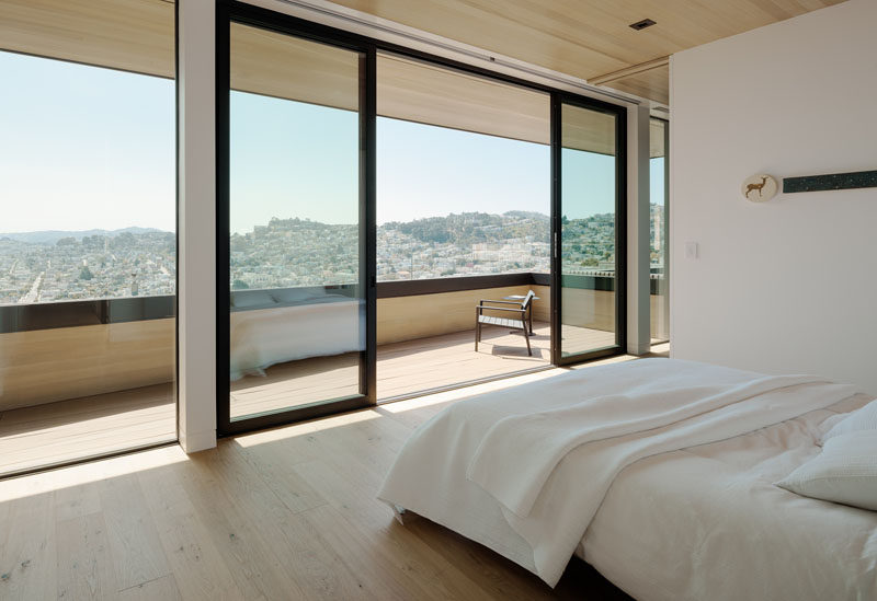In this modern bedroom, sliding glass doors open to a covered balcony that provides views of the surrounding area. #Balcony #Bedroom #SlidingDoors