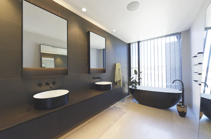 In this modern bathroom, a contrasting color palette has been used, with the exterior of the bathtub complementing the dark grey wall tiles and a dark vanity, while the floor and ceiling has been kept light. #ModernBathroom #BathroomDesign
