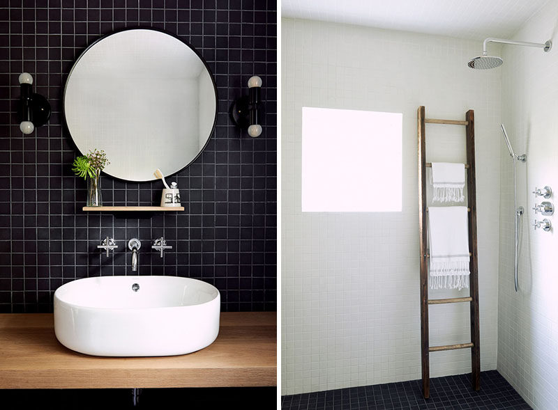 In this modern bathroom , square black tiles contrast the white walls, while a wood vanity and ladder by the shower adds natural touches. #Bathroom #ModernBathroom #MinimalistBathroom