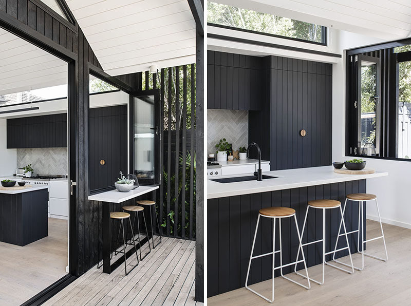 Large sliding doors and folding windows connect the new interior spaces, like the kitchen, living room, and dining room with the backyard. #BlackSiding #ModernKitchen #Bar #BlackKitchen