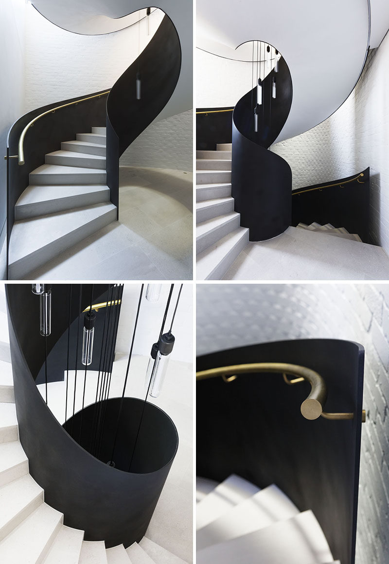 A freestanding steel plate and limestone spiral staircase leads visitors from the entryway up to the main social areas of this modern house. #SpiralStaircase #SpiralStairs