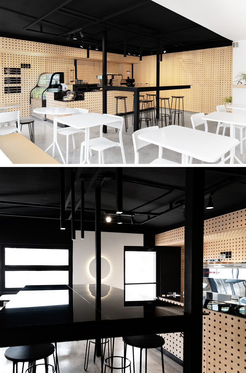 This modern coffee shop interior combines perforated wood walls with a black ceiling and accents, concrete flooring, and white furniture and walls. #CoffeeShop #CafeDesign #Interiors