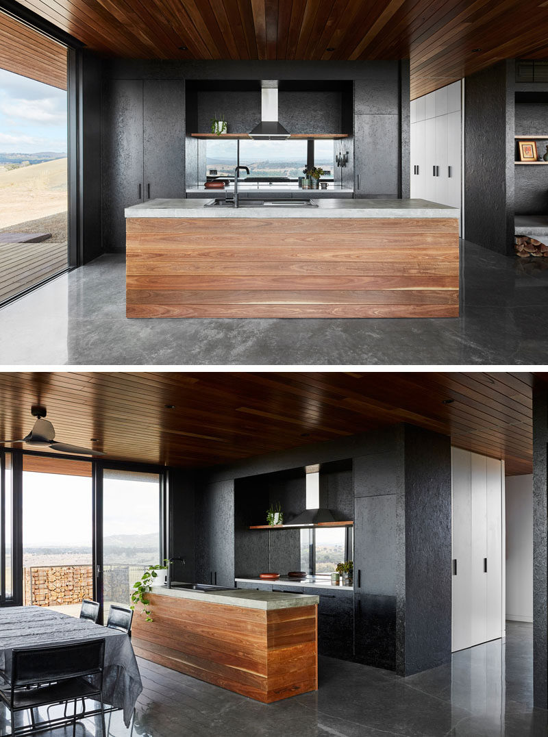 Spotted gum has been used on the ceiling and for the cabinetry throughout this modern house, while oriented strand board bracing is appropriated as wall lining and cupboard fronts. #BlackKitchen #BlackAndWood #ModernKitchen