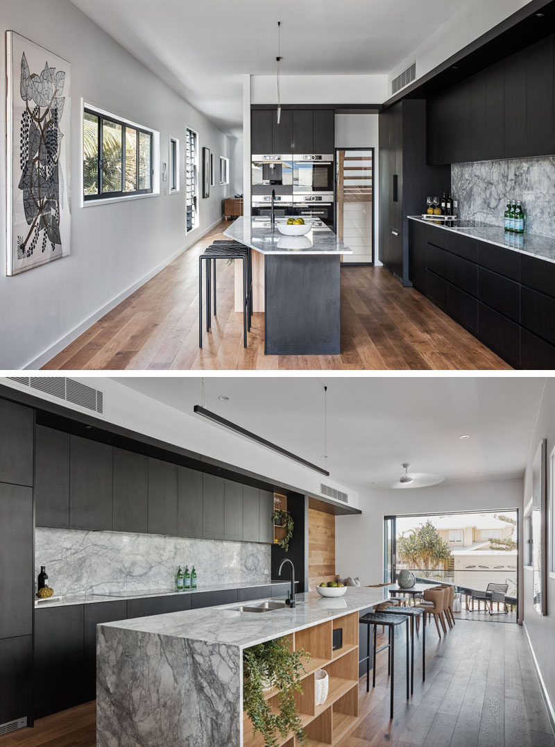 This modern kitchen features black cabinetry and an island with open shelving and seating on one side. #ModernKitchen #BlackKitchen #BlackCabinets