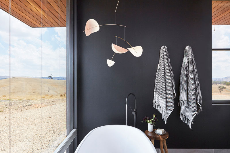 In this modern bathroom, dark walls contrast the freestanding white bathtub, and allow the natural views to be the focus of the room. #ModernBathroom #BlackBathroom