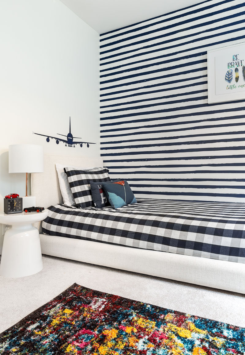 This updated modern boy's bedroom has been inspired by lived-in comfort of varsity sweats, a monochromatic palette of indigo-blues mixed with bold hints of copper, clean navy stripes, and natural tan leathers. #BoysBedroom #KidsBedroom #BedroomDesign