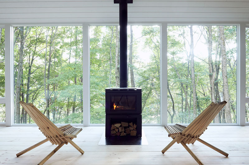 This modern cabin features black fireplace in front of large windows with tree views.#Fireplace #Windows #ModernCabin