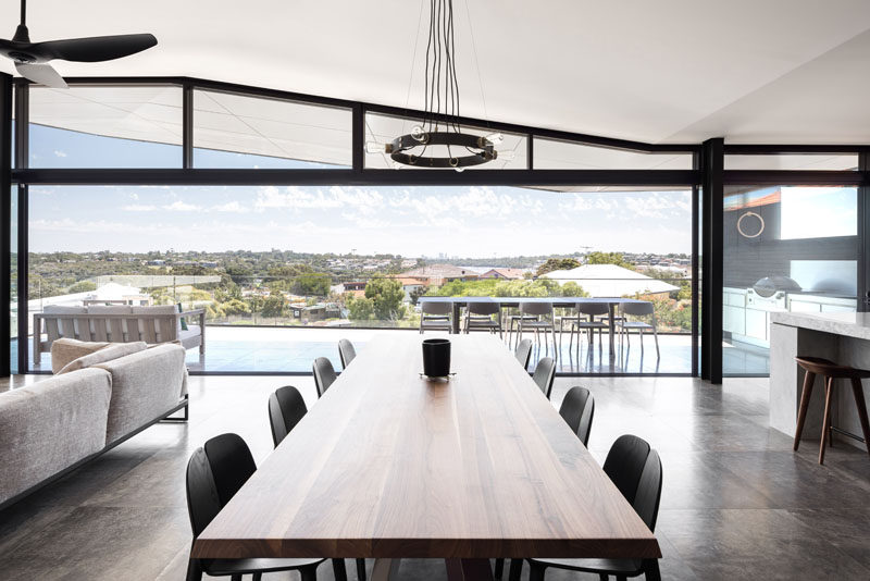 The balcony provides expansive views from the elevated position of this modern house, and enough room to have an outdoor lounge and dining area, as well as an outdoor kitchen with a BBQ. Inside, the large wood dining table separates the living room from the kitchen. #ModernInterior #DiningRoom #Balcony #OutdoorKitchen