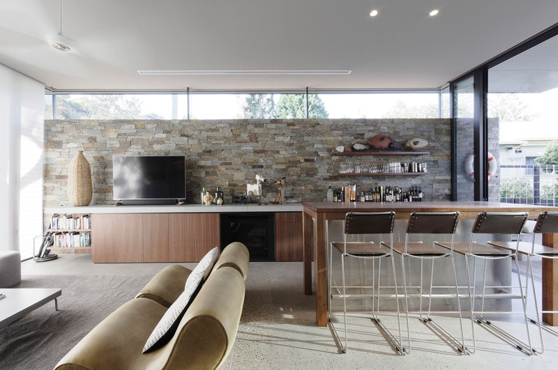 This modern games room has a stone wall, a bar that sits adjacent to a lounge, and sliding doors that open to an outdoor space. #GamesRoom #StoneWall #Bar